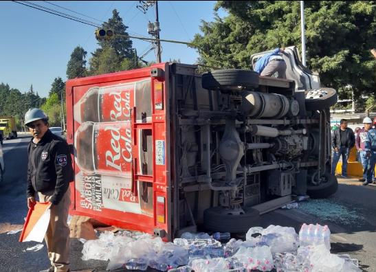 Vuelca camión repartidor de refrescos en Puebla capital; chofer queda atrapado